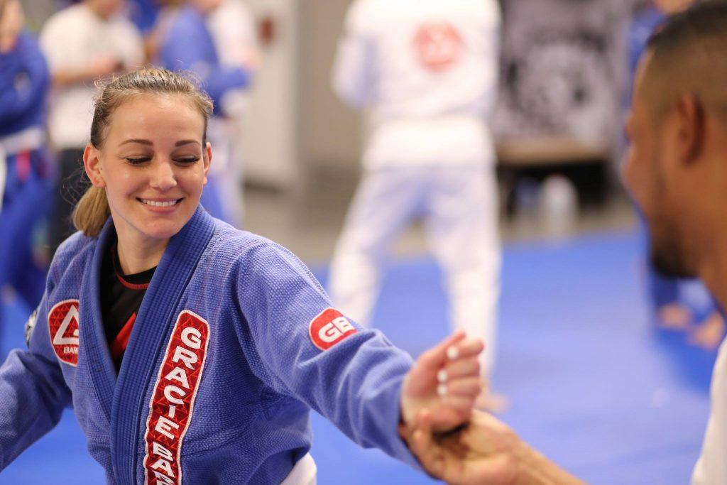 Woman practices a defensive BJJ technique at Gracie Barra