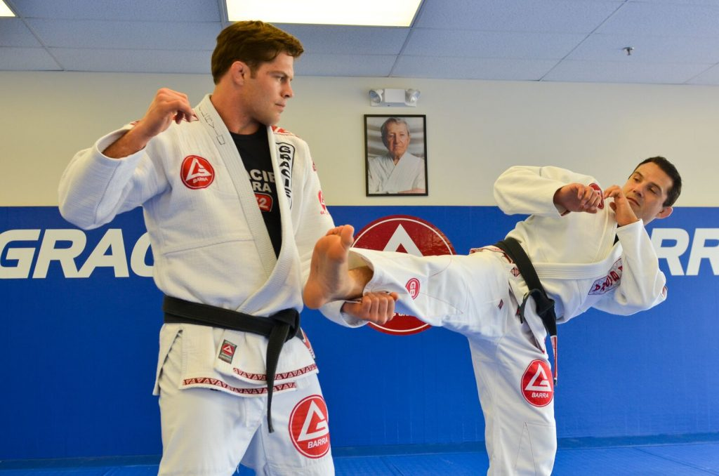 Two BJJ fighters grapple on the mat at Gracie Barra in Phoenix, AZ